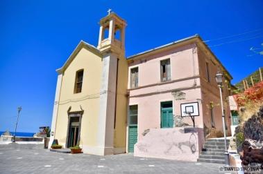 L'église de Pollara se situe au centre du village. A sa droite est érigée une fresque sur laquelle sont peints les personnages principaux du film Il Postino. © David Trotta
