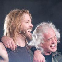 Les Foo Fighters remplissent le Wembley Stadium de Londres en 2008. Pour l'occasion, ils sont rejoints sur scène par John Paul Jones et Jimi Page de Led Zeppelin. De gauche à droite : John Paul Jones, Taylor Hawkins, Jimmy Page et Dave Grohl. Image wikimedia commons.